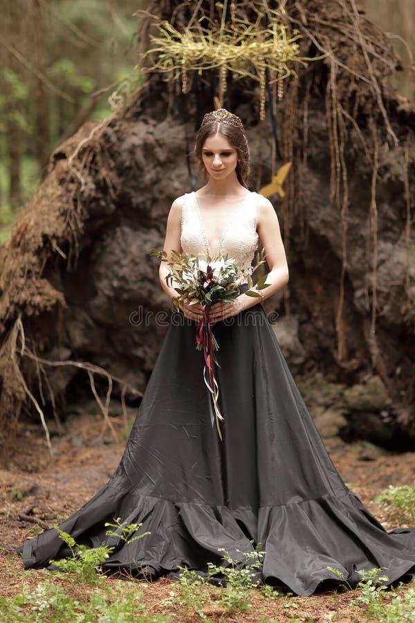 Noiva nova pensativa com o ramalhete no fundo da floresta fotos de stock