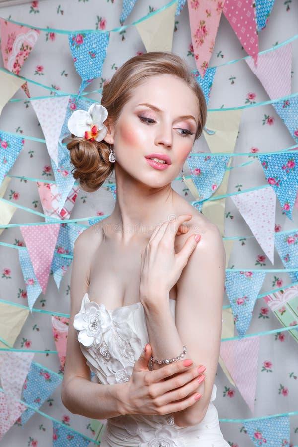 Noiva O modelo de forma novo com pele perfeita e compõe, flores no cabelo Mulher bonita com composição e penteado no quarto fotografia de stock