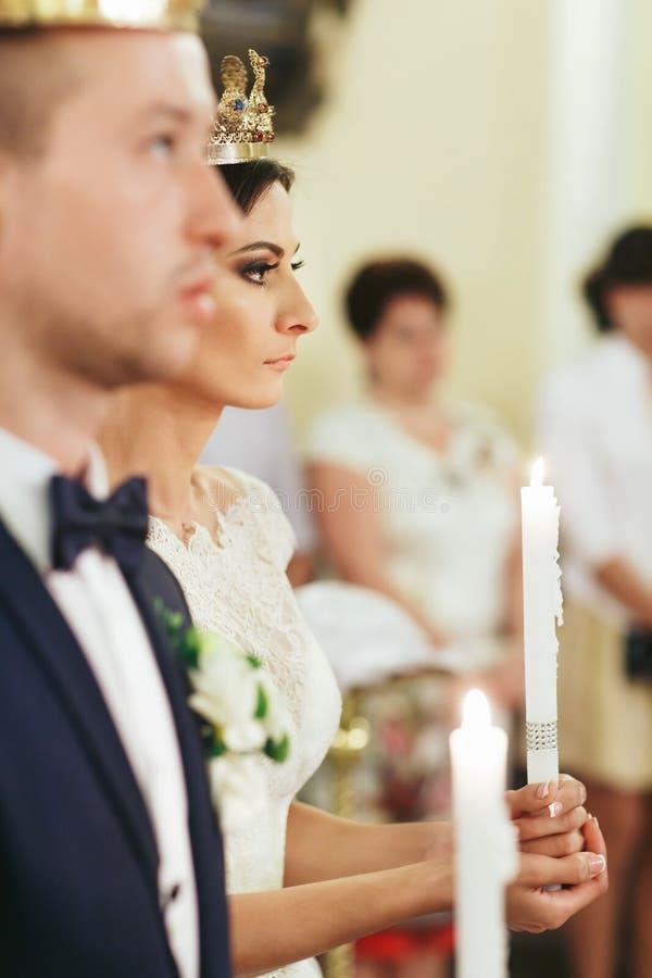A noiva olha seriamente guardando uma vela em seus braços durante o ce fotos de stock royalty free