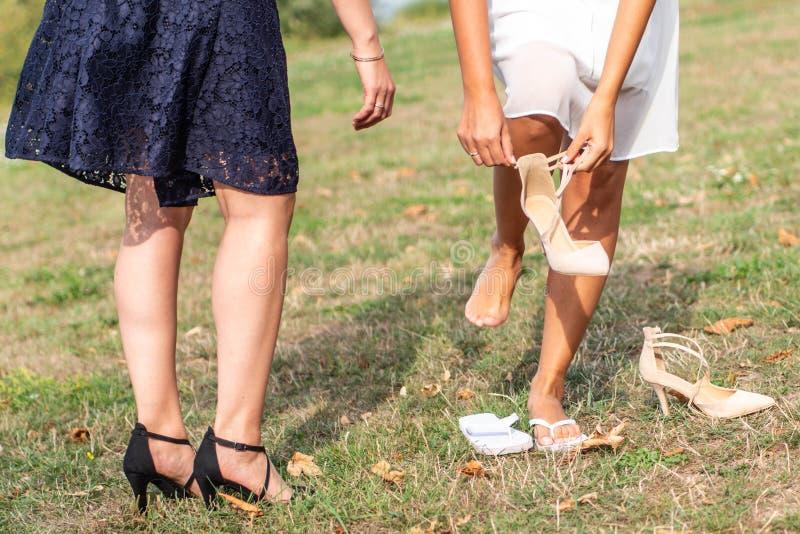 A noiva põe sobre sapatas do casamento sobre seus pés macios com sua empregada doméstica de honra foto de stock royalty free