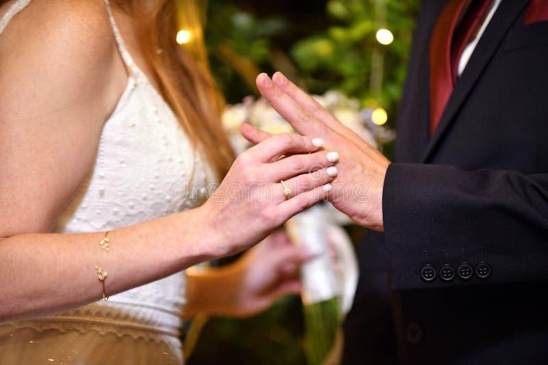 A noiva põe uma aliança de casamento sobre o noivo sob o chuppah em um casamento judaico tradicional fotografia de stock