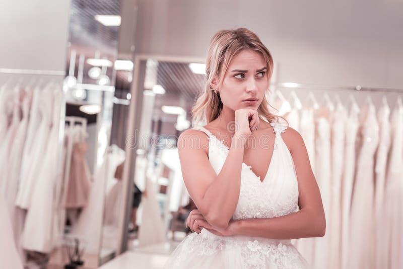 Noiva pensativa bonita que vem o boutique do casamento imagens de stock royalty free