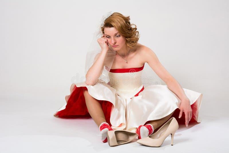 Noiva pensativa que senta-se no assoalho nas peúgas contra foto de stock royalty free