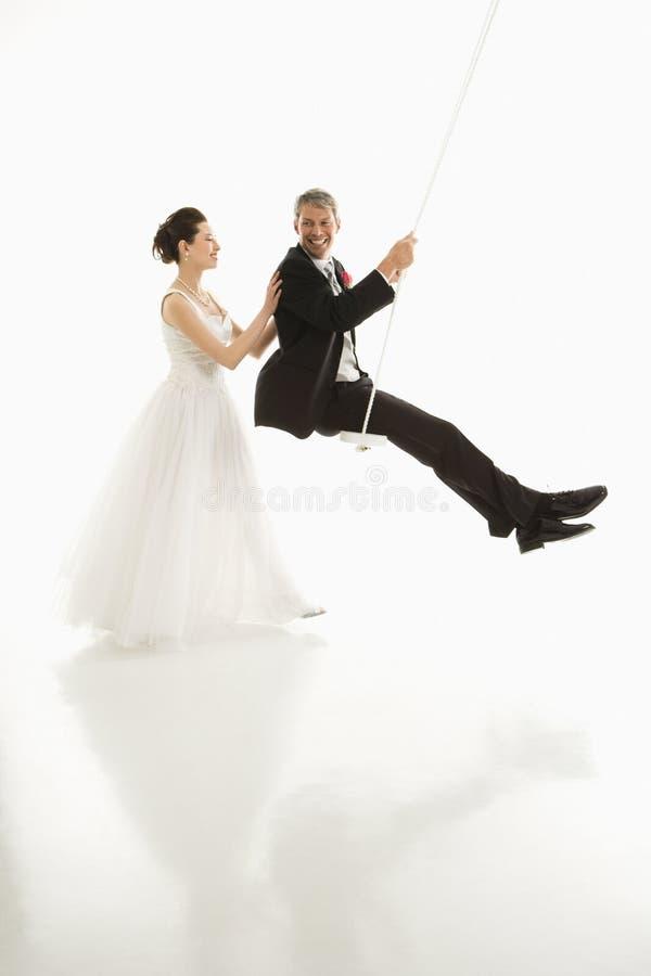 Noiva que empurra o noivo no balanço. imagem de stock royalty free