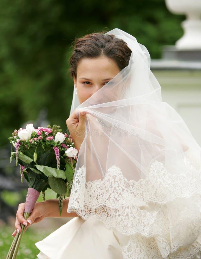 Noiva que esconde atrás de seu véu imagens de stock royalty free