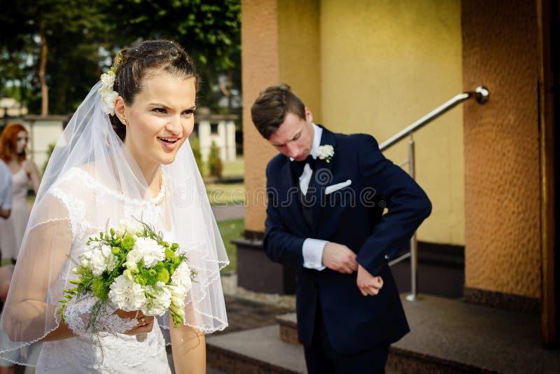 Noiva que está na frente da igreja que guarda um ramalhete nupcial fotografia de stock royalty free