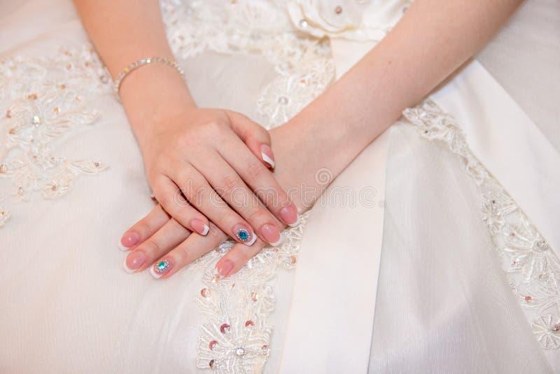 Noiva que guarda as mãos na frente do vestido foto de stock