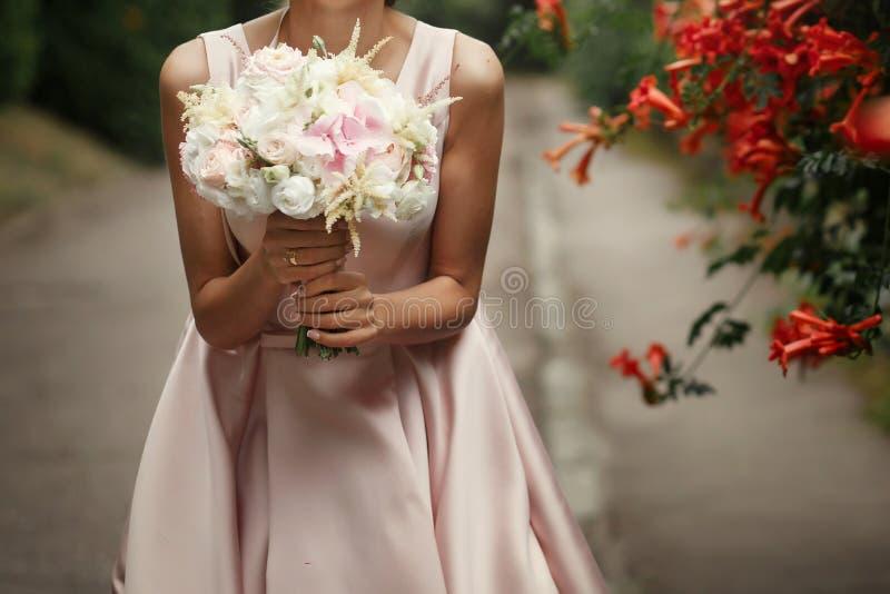 Noiva que guarda o ramalhete do casamento de rosas cor-de-rosa e das flores brancas dentro foto de stock royalty free