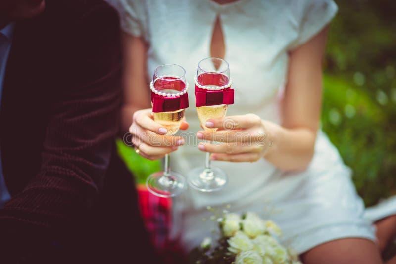 Noiva que guarda os vidros do champanhe, decorados com as fitas e as pérolas roxas do cetim, feriado das noivas imagem de stock royalty free
