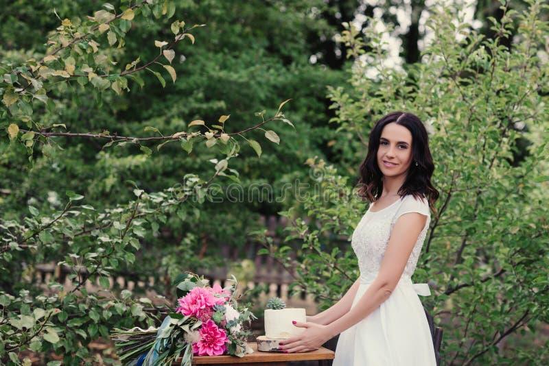 A noiva que guarda um bolo de casamento branco decorou flores imagem de stock