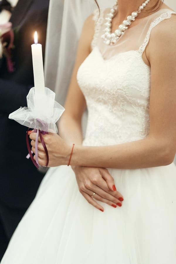 Noiva que guarda a vela na igreja na cerimônia de casamento, spir do casamento imagem de stock royalty free