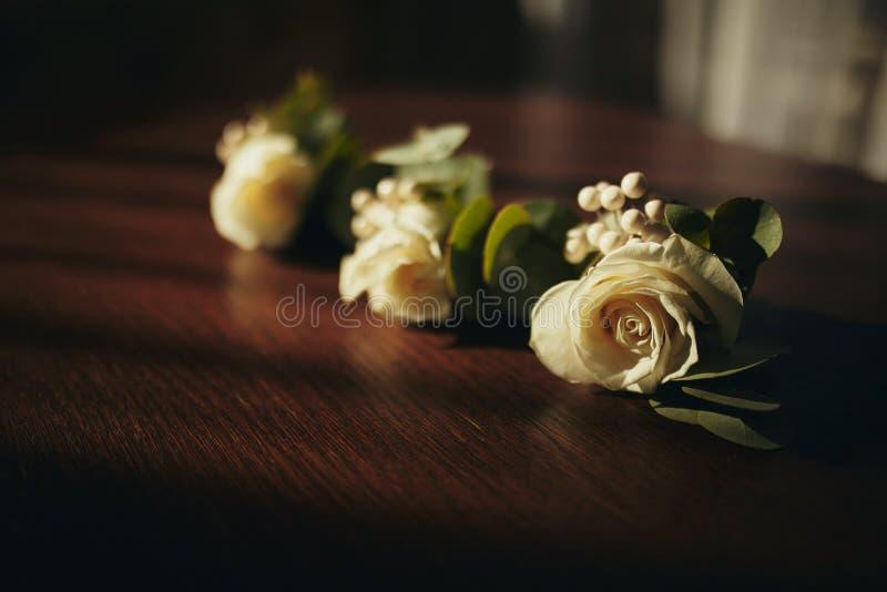 A noiva que guardam à disposição o close-up as flores da casa de botão do noivo com rosas brancas, e verde e hortaliças imagens de stock