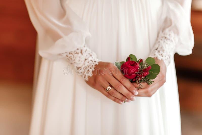 A noiva que guardam à disposição o close-up as flores da casa de botão do noivo com rosas brancas, e verde e hortaliças imagem de stock