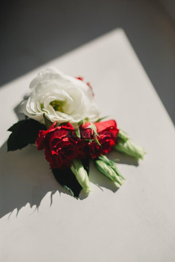 A noiva que guardam à disposição o close-up as flores da casa de botão do noivo com rosas brancas, e verde e hortaliças imagens de stock royalty free