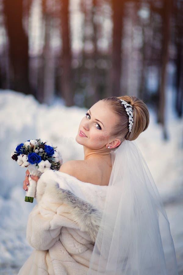 Noiva que levanta na floresta do inverno em um casaco de pele Sessão de foto do casamento em um parque nevado fotografia de stock royalty free