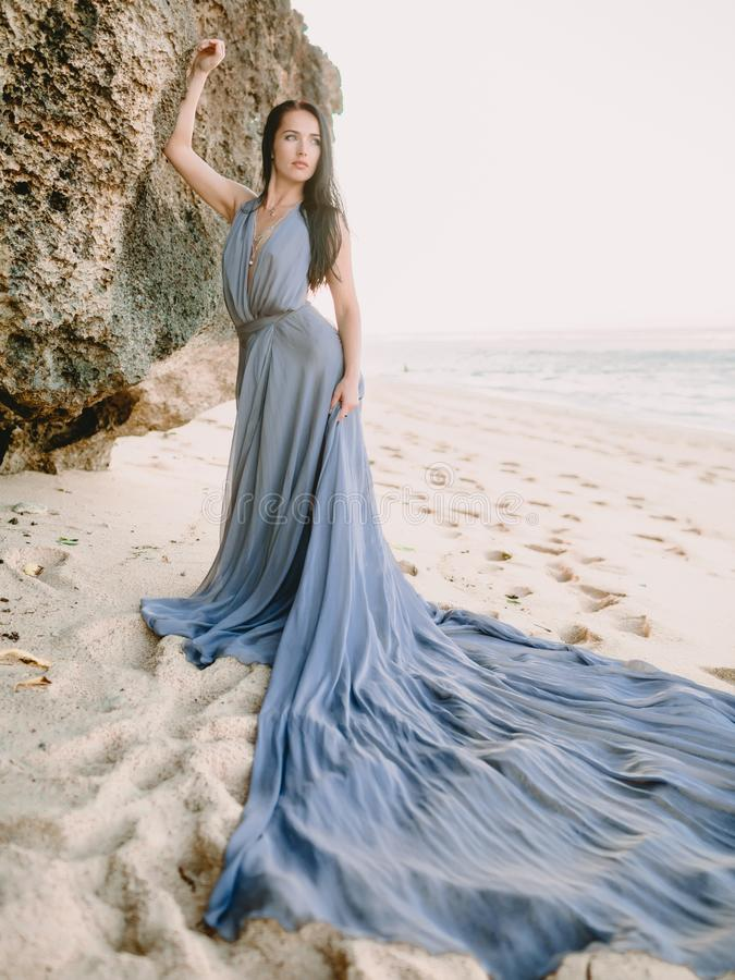 Noiva que levanta no vestido de casamento na praia em cores do por do sol ou do nascer do sol Estilo do casamento fotos de stock royalty free