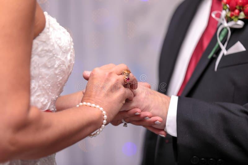 Noiva que põe o anel sobre o dedo do noivo durante a cerimônia de casamento foto de stock royalty free