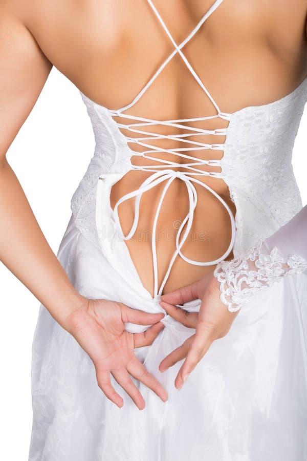 A noiva que põem sobre seu vestido de casamento branco, as mãos do close up e o laço vestem-se jovem mulher que amarra acima de s fotografia de stock royalty free