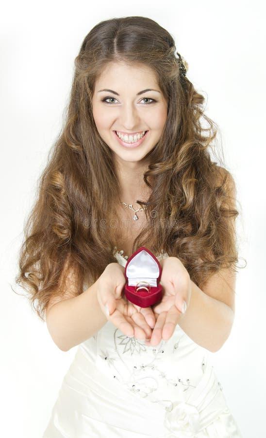 Noiva que prende a caixa vermelha com anéis de casamento dourado. fotografia de stock royalty free