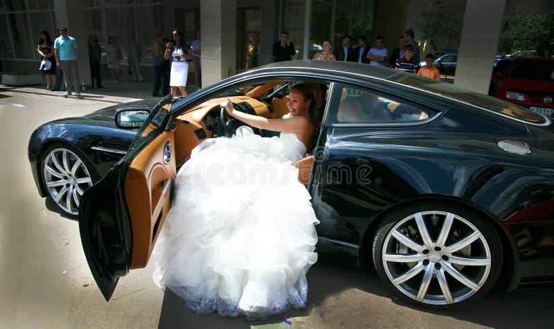Noiva que senta-se no assento de motorista de um carro de esportes poderoso imagens de stock