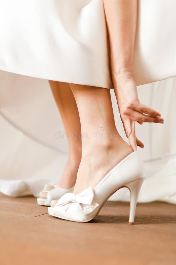 Noiva que veste suas sapatas do casamento - brancas com fita fotografia de stock royalty free