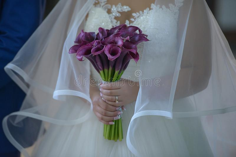 Noiva que veste um vestido de casamento opulento com o grande véu do tule e que guarda um ramalhete nupcial sofisticado dos lírio fotografia de stock