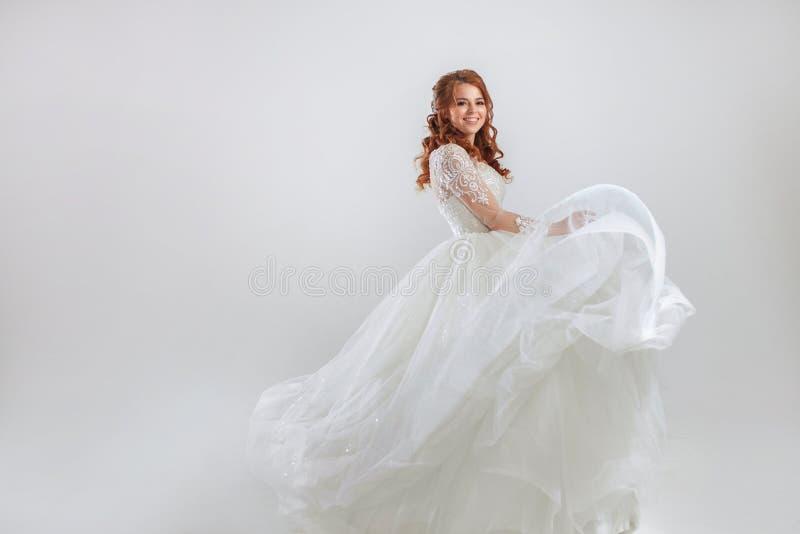 Noiva ruivo deliciosa em um vestido luxuoso Fundo claro foto de stock royalty free