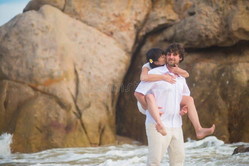A noiva senta-se na parte traseira do ` s do noivo contra as rochas e a água do mar fotografia de stock royalty free