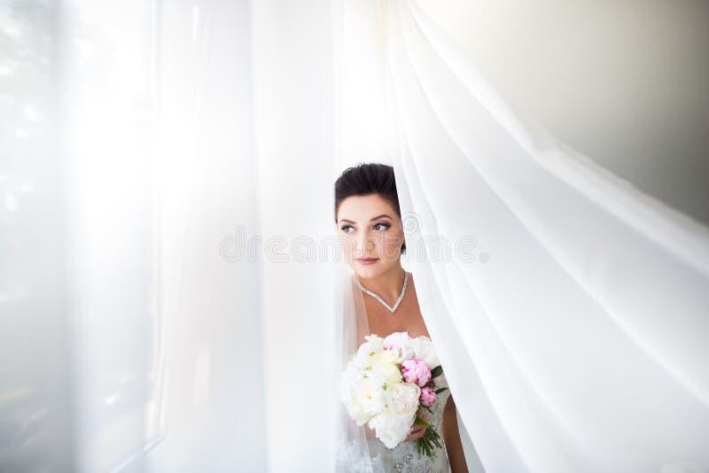 Noiva 'sexy' bonita no vestido branco que levanta sob a cortina fotografia de stock