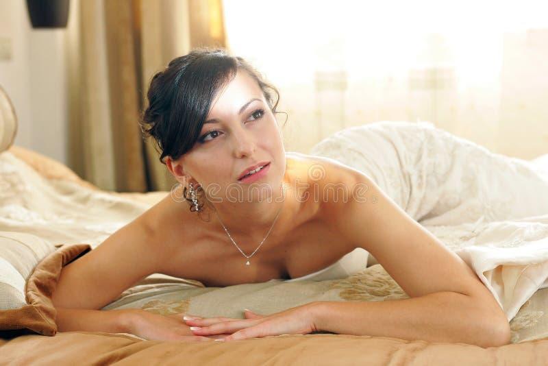 Noiva 'sexy' na lua de mel da cama foto de stock