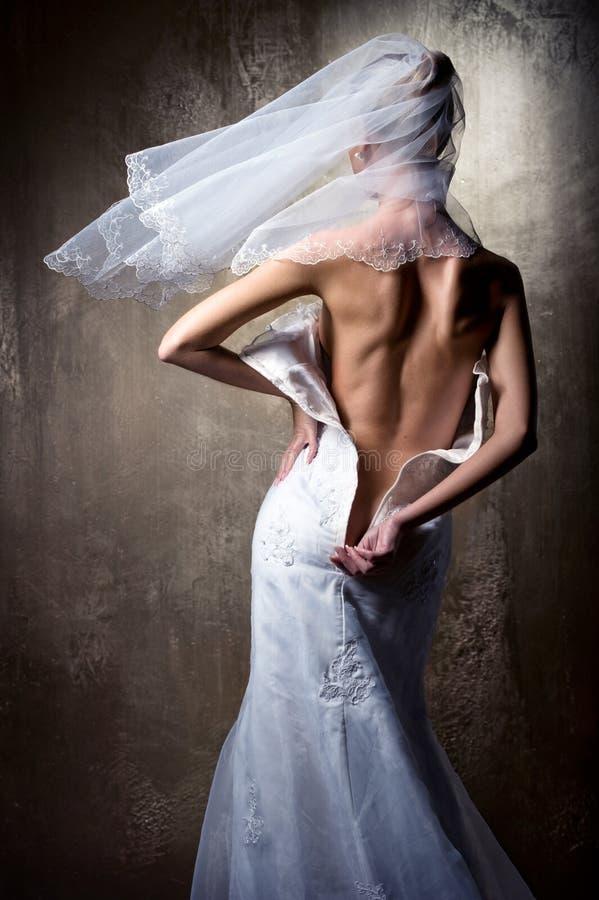 A noiva unzip seu vestido de casamento fotografia de stock