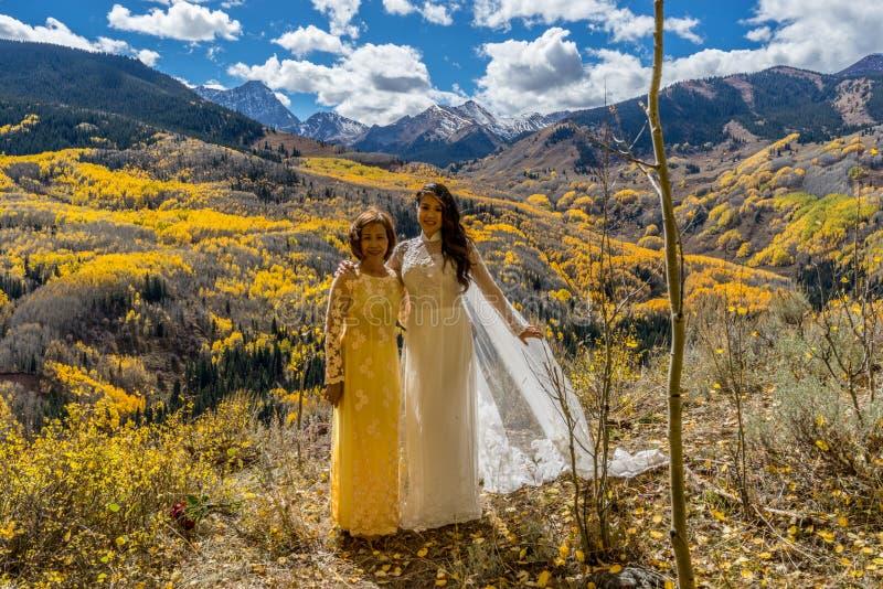 Noiva vietnamiana asiática com a mãe em vestidos de casamento vietnamianos tradicionais nas árvores amarelas do álamo tremedor do fotografia de stock