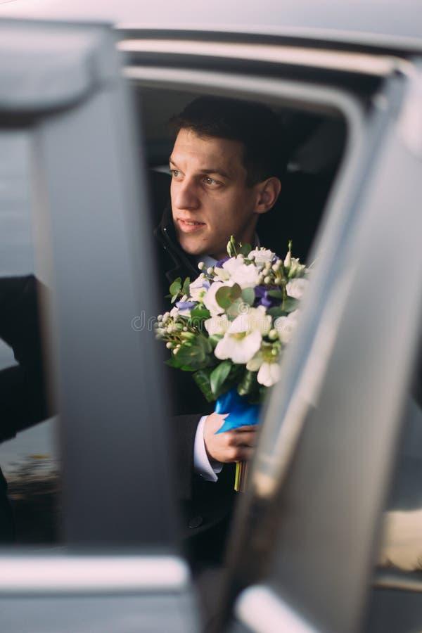 Noivo à moda considerável com o ramalhete no carro do casamento imagem de stock