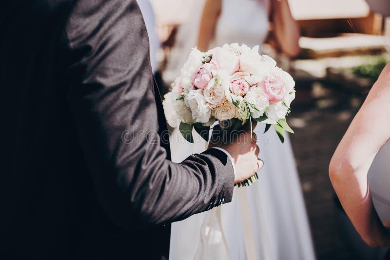 Noivo à moda no terno preto que guarda o ramalhete moderno do casamento de rosas e de peônias cor-de-rosa macias para a noiva na  imagem de stock royalty free