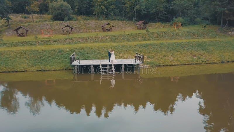 Noivo com a noiva perto do lago no parque Pares do casamento Tiro a?reo fotografia de stock royalty free