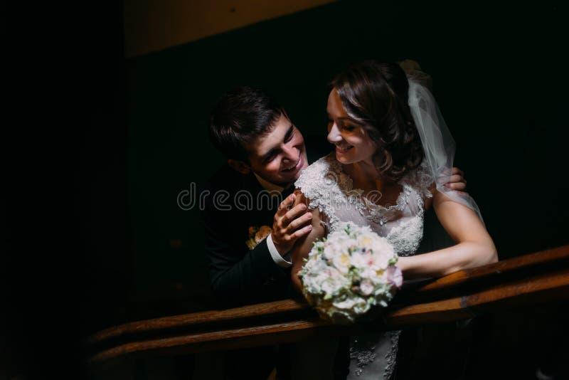 Noivo considerável abraçando de trás de sua noiva sensual bonita que guarda o ramalhete nas escadas de madeira, close-up imagens de stock royalty free