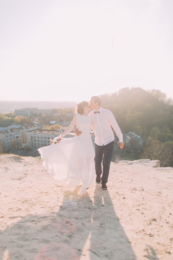 Noivo considerável na camisa branca e na noiva que vestem o beijo de passeio do vestido nupcial contra o contexto da cidade imagens de stock royalty free