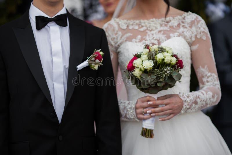 Noivo considerável no terno preto e noiva à moda que guarda o casamento b imagens de stock