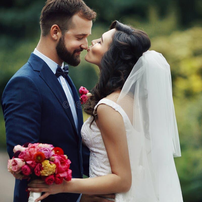 Noivo considerável que abraça a noiva bonita com o ramalhete em romântico foto de stock