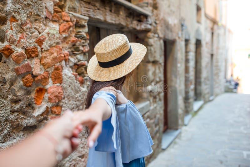Noivo depois da amiga que guarda as mãos na rua europeia velha que ri e que sorri fotografia de stock royalty free