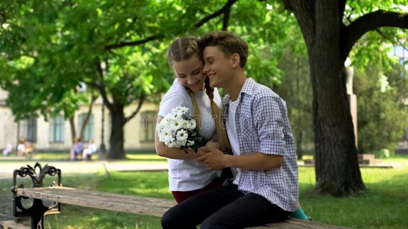Noivo e amiga que abraçam, menino que apresenta o ramalhete das flores, data fotografia de stock