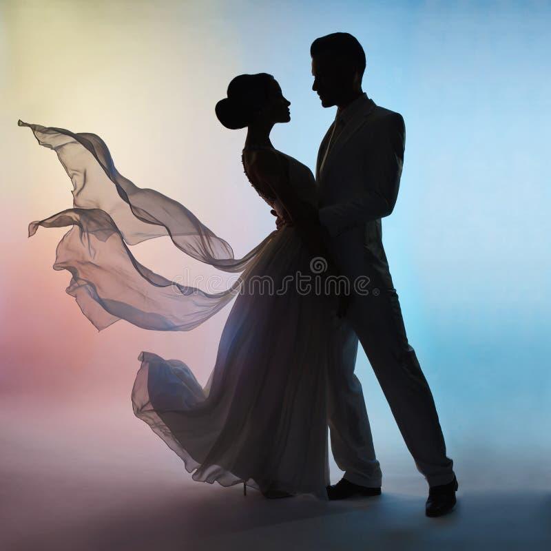 Noivo e noiva da silhueta dos pares do casamento no fundo das cores imagens de stock