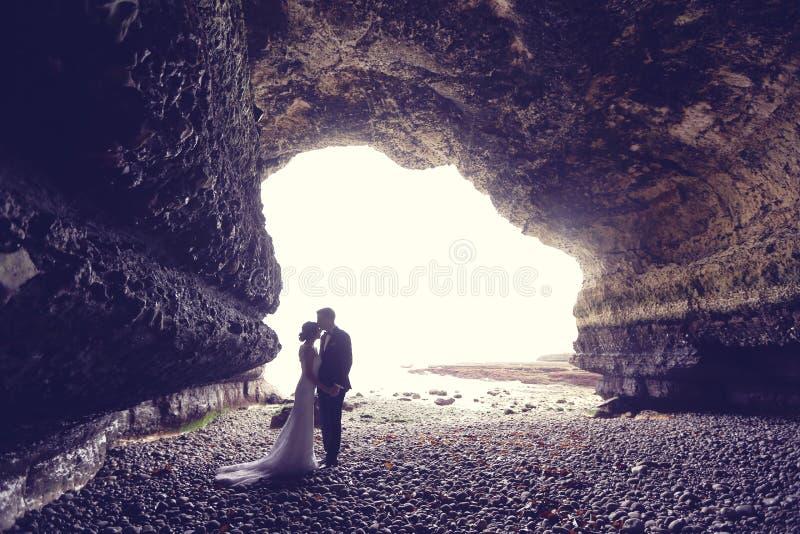 Noivo e noiva em uma caverna fotografia de stock royalty free