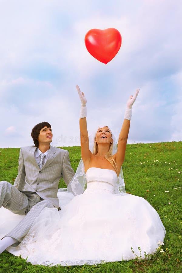 Noivo e noiva; a noiva joga o balão imagem de stock royalty free