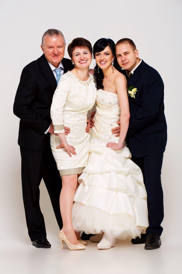 Noivo e noiva positivos com pais fotografia de stock