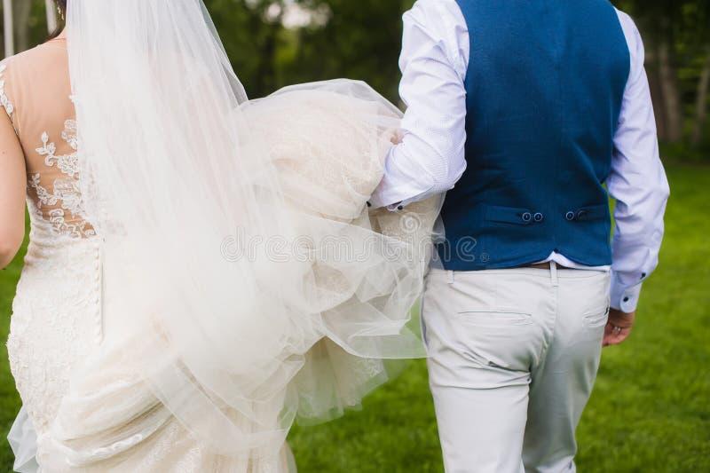 Noivo e noiva que correm afastado imagem de stock