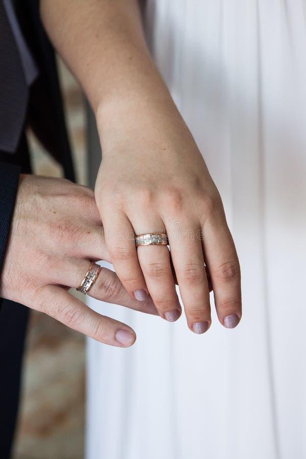 Noivo e noiva que guardam as mãos com alianças de casamento foto de stock