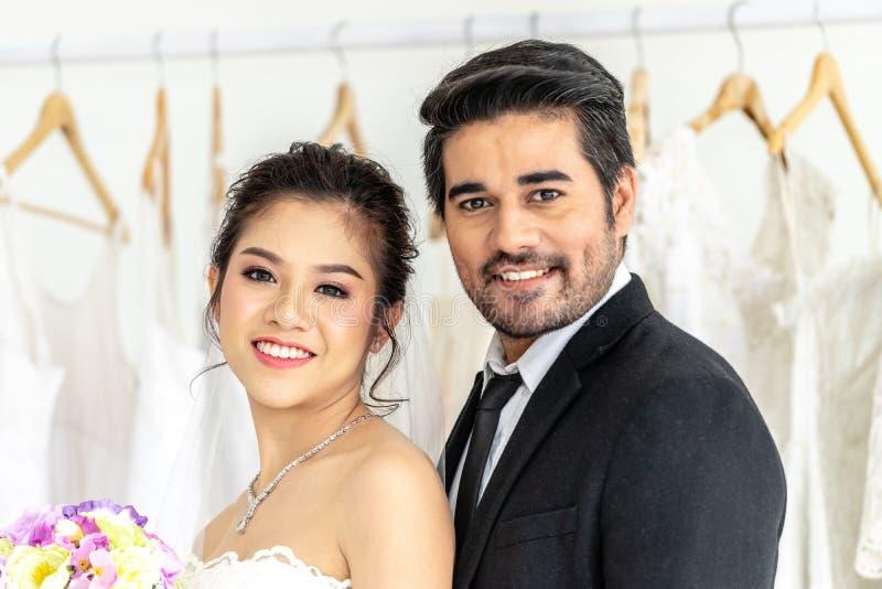 Noivo e noiva que levantam junto na loja do casamento foto de stock