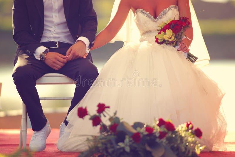Noivo e noiva que sentam e que guardam as mãos imagens de stock