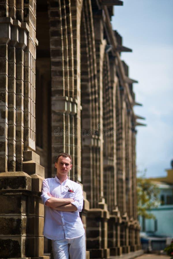 Noivo em uma camisa branca que levanta perto das colunas de pedra da igreja Católica foto de stock royalty free